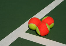 Three balls in a corner. Yellow-red balls on a green tennis court Royalty Free Stock Photo