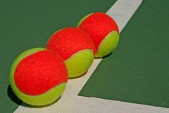 Three balls on a green court Stock Images