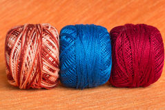 Three balls of a multi-colored yarn on an orange background Stock Photos