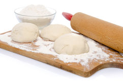 Three balls of pizza dough with a cup of flour and a rolling pin Stock Photo