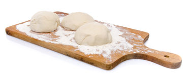 Three balls of pizza dough on a wooden board Royalty Free Stock Images