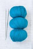 Three balls of yarn and knitting needles Royalty Free Stock Photos
