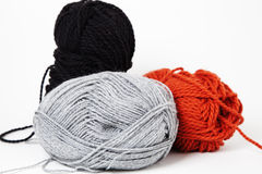 Wool yarns. Three balls of yarns coloured grey, orange and black Royalty Free Stock Photo