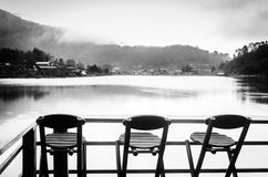 Three bamboo chairs on a village mountain lake Royalty Free Stock Photography