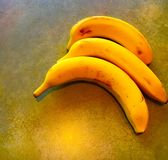 Three Bananas. Three bright yellow bananas on a table Royalty Free Stock Photo