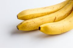 Three bananas on a white background in the corner frame of the photo. Stock Images