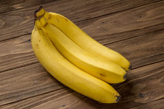 Three bananas  on wooden background Royalty Free Stock Photos