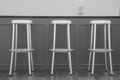 Three bar chairs in front of a bar. Three aluminum bar chairs placed in front of a grey bar Royalty Free Stock Photo