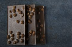 Three bars of delicious dark chocolate on table royalty free stock photo