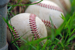 Three Baseballs. A group of three baseballs in the grass next to the fence Royalty Free Stock Photos