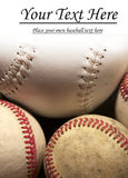 Three baseballs and softball with copy space. A close up of three baseballs and a softball nestled together with the top fading to white for copy space Royalty Free Stock Photo