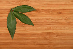 Three bay leaves in bamboo wooden board corner Stock Images