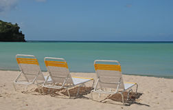 Three on the Beach. Three empty lounge chairs on a tropical island beach Royalty Free Stock Photography