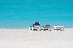Three beach chairs in a lonely beach. With clear blue water Royalty Free Stock Images