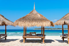 Three beach house on the sandy coast of blue sea Royalty Free Stock Photos