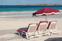 Three beach loungers and umbrella on sand Royalty Free Stock Photo