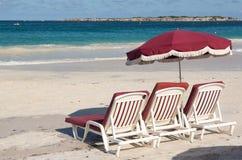 Three beach loungers and umbrella on sand. Three white plastic beach loungers and umbrella on Orient Beach St Martin royalty free stock photo