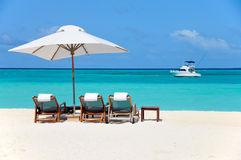 Three beachchairs and yacht Royalty Free Stock Image