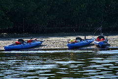 Three beached blue kayaks. With fishing poles stock photography