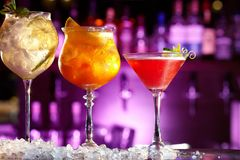 Three beautiful alcoholic cocktails with fruit. Three beautiful alcoholic cocktails with fruit, on the background of the bar stand with beautiful backlighting royalty free stock image