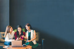Three beautiful Asian girls using smartphone and laptop, chatting on sofa at cafe with copy space stock images