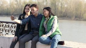 Three beautiful Asian teenagers taking a funny selfie with their smartphone. stock footage