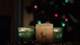 Three beautiful candles on background of flashing Christmas tree. 4k. three beautiful candles standing on the table against the background of flashing Christmas stock video