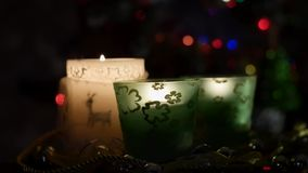 Three beautiful candles on background of flashing Christmas tree stock video footage