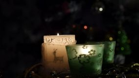 Three beautiful candles on background of flashing Christmas tree. Slider. 4k. three beautiful candles standing on the table against the background of flashing stock footage