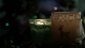 Three beautiful candles on background of flashing Christmas tree. Slider.three beautiful candles standing on the table against the background of flashing stock video