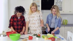 Three beautiful caucasian girls cooks fresh salad at the kitchen stock video footage