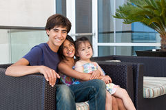 Three beautiful children sit happily together Stock Photography