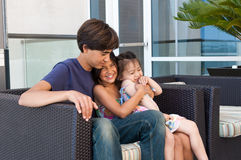 Three beautiful children sit happily together Stock Images