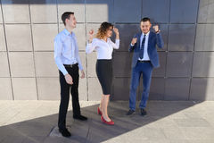 Three beautiful energetic people laugh, rejoice success, smiling Royalty Free Stock Photography