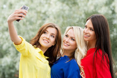 Three beautiful female friends being modern by taking selfies Stock Photos