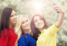 Three beautiful female friends being modern by taking selfies. Royalty Free Stock Image