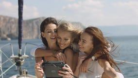 Three beautiful female friends make selfie on a yacht. Three beautiful sexy female friends make fun and selfie on luxury yacht in open sea Stock Image