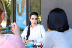 Three beautiful female smile in cafe, talk, tell secrets, eat, d Royalty Free Stock Photography