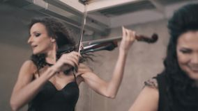 Three beautiful female violinist playing the violin in a smoke-filled room. Very nice shots. Great performance stock video footage