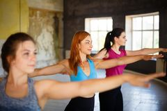 Three beautiful fit woman dancing zumba in class royalty free stock photography