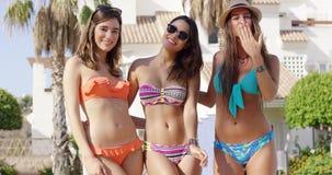 Three beautiful friends wearing colorful bikinis stock video