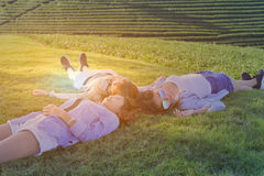 Three beautiful girl are laying on the sunny glade with smail an. Three beautiful asian girls are laying on the sunny glade with smail and close eyes.Dress in Stock Photos
