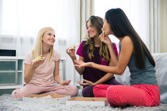 Three beautiful girlfriends eating pizza Royalty Free Stock Photography