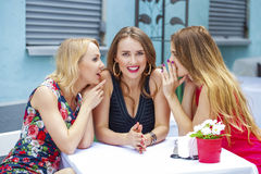 Three beautiful girlfriends gossiping woman sitting at a table i Royalty Free Stock Photography
