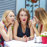 Three beautiful girlfriends gossiping woman sitting at a table i Stock Photography