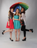 Three beautiful girls acting up under one umbrella Royalty Free Stock Image