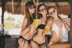 Three beautiful girls in a bar on the beach Stock Photography