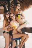 Three beautiful girls in a bar on the beach stock images