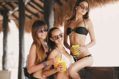 Three beautiful girls in a bar on the beach Royalty Free Stock Images