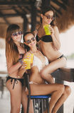 Three beautiful girls in a bar on the beach Royalty Free Stock Photography